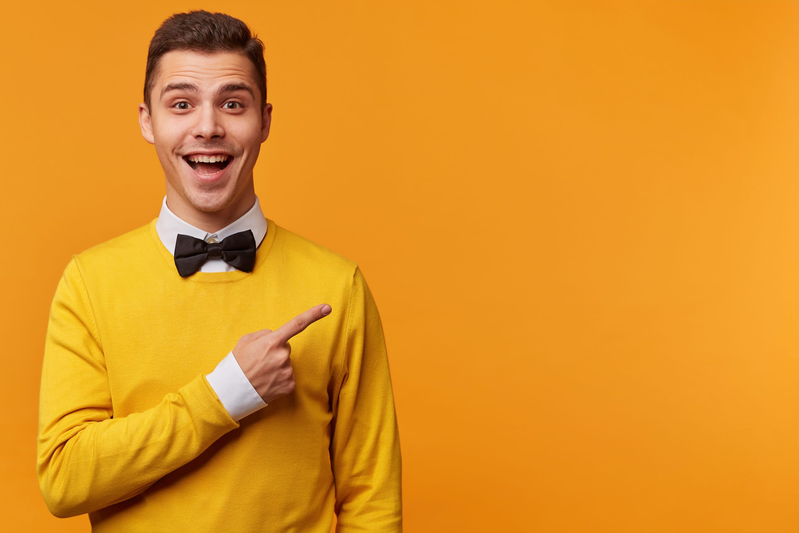 glad-happy-man-yellow-sweater-white-shirt-black-bow-tie-pointing-right-with-his-finger-scaled
